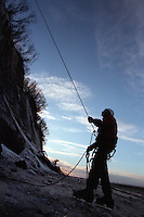 The day comes to an end as an ice climber belays for a partner on the Cook Inlet beach near Ninilchik, Alaska. Ice climbing is one of many winter sports and activities popular on the Kenai Peninsula.