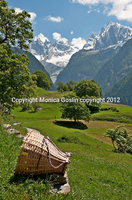 A traditional basket used to gather hay sits by a road in Soglio, Switzerland a town the Bregaglia Valley that leads past barns, agricultural fields and hiking trails; Graubunden Canton