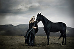 Female youth wearing a black satin gown and standing next to a black horse.