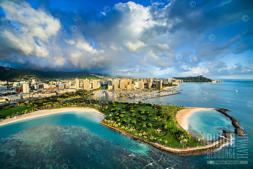 An aerial perspective of Magic Island, with Ala Wai Yacht Harbor, Waikiki and Diamond Head in the distance, Honolulu, O'ahu.