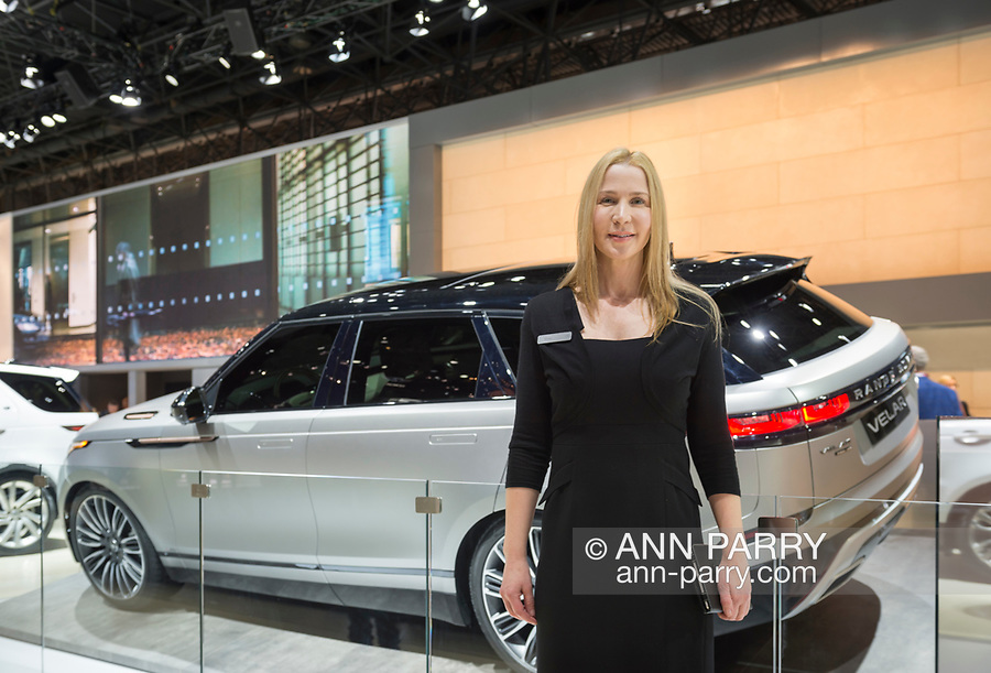 """Manhattan, New York, USA. April 12, 2017. Female rep stands in front of Land Rover 2018 Range Rover VELAR, medium SUV, makes its North Amerian launch at the New York International Auto Show, NYIAS, during the first Press Day at the Javits Center. The Latin word """"velare"""" means to veil or cover, and Velar was what Range Rover engineers called pre-production prototypes Range Rovers in the 1960s."""
