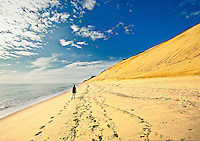 Woman walking aon beach along huge sand dune cliffs at Long Nook Beach, Cape Cod National Seashore, Truro, Cape Cod, MA, USA