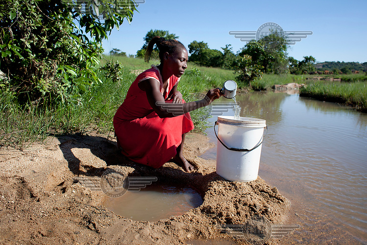 Mrs Ida Bere, 40 collects water from a local river bed. <br /> She says: 'It is very difficult for me and my family. I've got teenage girls that I send from home to fetch water and it's quite a distance. My fear is that it's very dangerous having a girl child moving around, passing through thick forest and hilly places. That scares me. I always have this fear that at any given time my two girls might face danger.<br /> 'The time that we are walking up and down to fetch water is productive time that is wasted. If we could get water nearer to our village it would reduce the amount of trips and that time could be used to do at least something that would uplift out livelihoods. <br /> 'We waste a lot of time going to clinics because we have to drink dirty water. That time would be useful. If our children were healthy that time could be used doing more productive activities.<br /> 'My girls are school going age, they need to read, do their homework and concentrate on their school work. But because they have to do these trips to fetch water, they don't have enough time to do this. That affects their performance at the end of the day. <br /> 'My hope is that if they could proceed with their education, get a good education, better their lives. My desire is that they go to school, they get a good education and they become better people.'