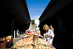 Lynn Eder shops for onions at the Sunday Certified Farmers' Market in Sacramento, California.