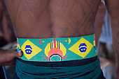 """Altamira, Brazil. """"Xingu Vivo Para Sempre"""" protest meeting about the proposed Belo Monte hydroeletric dam and other dams on the Xingu river and its tributaries. A Kamaiura belt using the Brazilian national flag."""