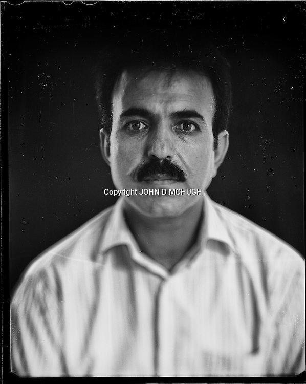 "Abdul Waheed Khalili, Director of the Turquoise Mountain Foundation, is seen in his office in Kabul, 26 August 2012. This portrait was shot on a 5x4 Linhof Technika IV, circa 1959, and a Schneider Kreuznach 270mm lens, circa 1952, with front tilt, and is part of a series entitled ""Putting an Afghan face on the war."" (John D McHugh)"