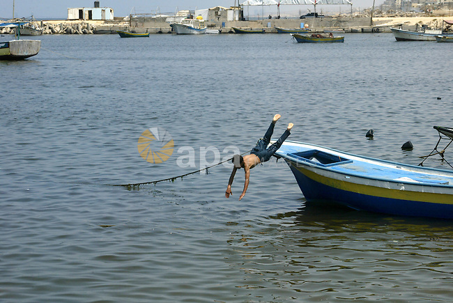 Palestinian boys enjoy swimming at the port of Gaza city on the sixth day of the holy month of Ramadan on August 16,2010. Photo by Ashraf Amra