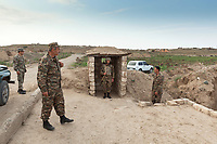 """Nagorno-Karabakh, also known as Artsakh, is a landlocked region in the South Caucasus. Merzili. A group of soldiers and an officer, all wearing camouflage uniforms. One soldier stands in a gatehouse. He has a bullet proof jacket, a helmet on his head and holds a Kalashnikov on the shoulder. All men are distant 1000 meters from the front line of the ongoing fighting with Azerbaijan. Nagorno-Karabakh is a disputed territory, internationally recognized as part of Azerbaijan, but most of the region is governed by the Republic of Artsakh (formerly named Nagorno-Karabakh Republic), a de facto independent state with Armenian ethnic population. The territory is under the control of the Artsakh Defense Army (which is backed up by Armenian Army) due to the ongoing territorial disputes with Azerbaijan. Merzili (also Mirasali) was a village and municipality in the Agdam Rayon of Azerbaijan. A Kalashnikov rifle is any one of a series of automatic rifles based on the original design of Mikhail Kalashnikov. They are officially known in Russian as """"Avtomat Kalashnikova"""" , but are widely known as Kalashnikovs, AK47s, or as a """"Kalash"""".  5.10.2019 © 2019 Didier Ruef"""