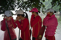 Women rowers cover their ears as firecrackers explode during a ceremony before their dragon boat practice at Jiujiang Dragon Boat Base in Nanhai district of Foshan city, Guangdong province, November 8, 2011.