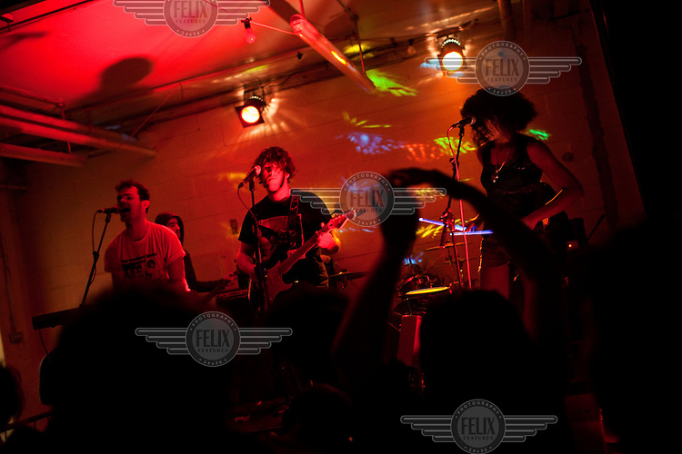 A rock band plays at a warehouse venue in London.