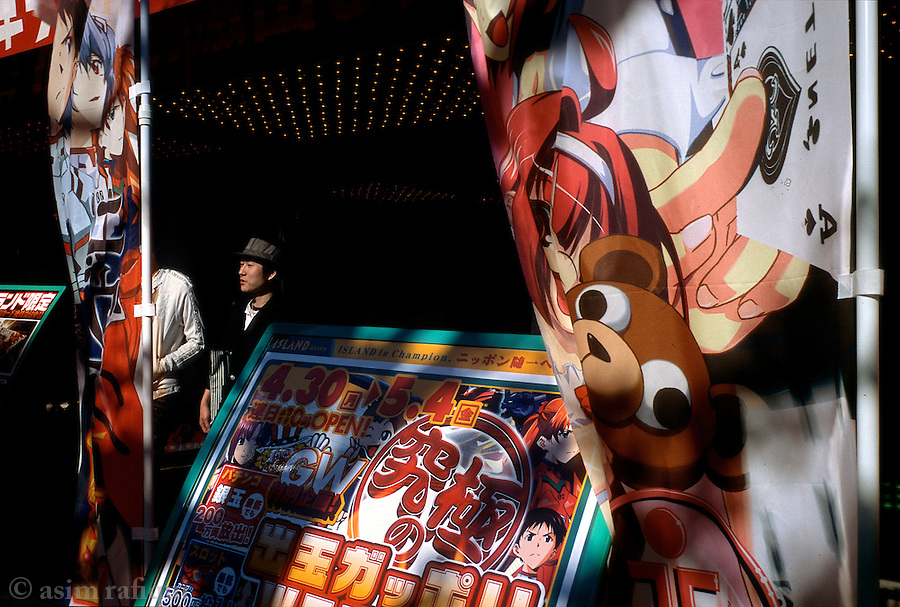 Young men outside a video game and electronic entertainment center.  The use of manga characters for advertising and promotions is very common as these appeal to the large number of manga fans that congregate in areas like Akihabara.