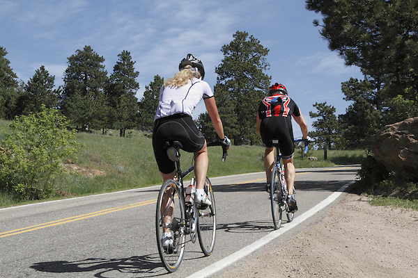Caucasian female and male biking uphill on Lookout Mountain Road west of Denver, Colorado, USA .  John leads private photo tours in Boulder and throughout Colorado. Year-round. .  John offers private photo tours in Denver, Boulder and throughout Colorado. Year-round.