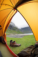 View from inside tent to the isolated Kvalvika beach during rainy weather, Lofoten islands, Norway