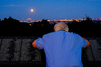 EAGLE ROCK, NJ - JUNE 09: A man tries to take a picture of the Strawberry Moon as it rises over lower Manhattan on June 06, 2017 in Montclair, New Jersey. Photo by VIEWpress/Eduardo MunozAlvarez