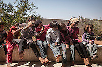 In this Sunday, Sep. 29, 2013 photo, a sister and cousins of Syrian child ABDU EL KADER (not pictured) are photographed at his family's house in Madaya village after attended classes in the public school in the Idlib province countryside of Syria. Children have come back to school in the rebel controlled territory despite the constant threaten of shelling and the ongoing fighting, and public schools still operating financially under the Syrian government administration. (AP Photo)