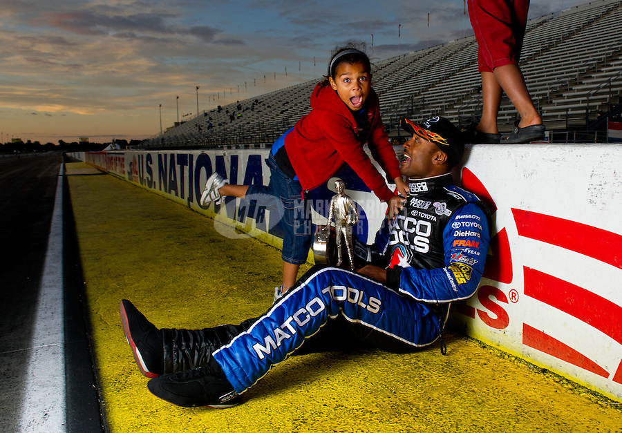 Sept. 5, 2011; Claremont, IN, USA: NHRA top fuel dragster driver Antron Brown poses for a portrait with daughter Arianna Brown after winning the US Nationals at Lucas Oil Raceway. Mandatory Credit: Mark J. Rebilas-
