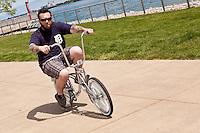 A man rides his byke on Detroit riverWalk Saturday June 8, 2013.  River Walk is a 9km promenade from the Ambassador Bridge to Belle Isle.