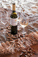 Glasses of local white wine are served on the dining table in the sand-floored cabin