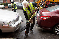 David Dollosa (right) and Aroll Victor fill potholes with asphalt while working for the Boston Public Works Department in Boston, Massachusetts, USA, on April 12, 2012. The city uses a computer system to track public complaints and record work done by city crews to mitigate these complaints.  A supervisor or inspector photographs before and after pictures of the work in addition to making notes about the work done.