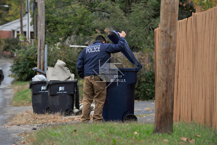 Major Case Squad investigators look for evidence in an alley near West Main Street in Belleville between 75th and 76th streets on Monday morning October 30, 2017. An 18 year-old male was found shot to death there late Sunday night.