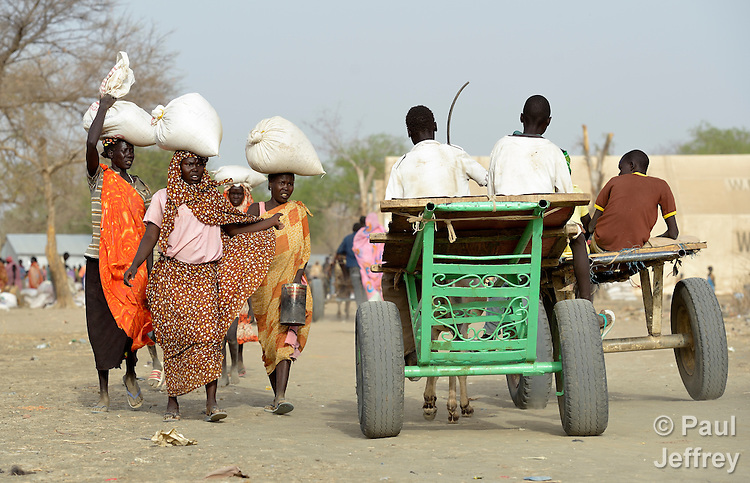 Women carry bags of sorghum on their heads in Agok, a town in the contested Abyei region where tens of thousands of people fled in 2011 after an attack by soldiers and militias from the northern Republic of Sudan on most parts of Abyei. Although the 2005 Comprehensive Peace Agreement called for residents of Abyei--which sits on the border between Sudan and South Sudan--to hold a referendum on whether they wanted to align with the north or the newly independent South Sudan, the government in Khartoum and northern-backed Misseriya nomads, excluded from voting as they only live part of the year in Abyei, blocked the vote and attacked the majority Dinka Ngok population. The African Union has proposed a new peace plan, including a referendum to be held in October 2013, but it has been rejected by the Misseriya and Khartoum.