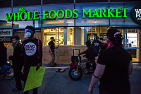 NEW YORK, NEW YORK - MAY 31: Men protect a Woole Foods store against protesters on May 31, 2020 in New York. Protests spread across the country in at least 30 cities in the United States. USA For the death of unarmed black man George Floyd at the hands of a police officer, this is the latest death in a series of police deaths of black Americans (Photo by Pablo Monsalve / VIEWpress via Getty Images)
