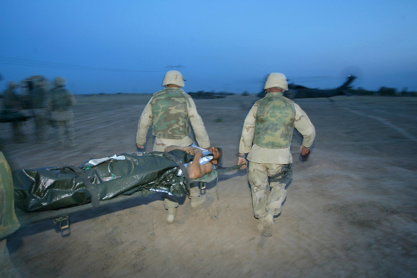 Kitrit, IRAQ--A suspect fighting with the Fadayeen is carried by US Marines to the awaiting MEDEVAC helicopter afet being treated for injuries sustain during a firefight with US Marines. He will be flown to another medical facility where he can be treated for his wounds.