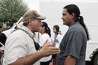 "Phoenix, Arizona (July 28, 2012) - About three hundred people marched to protest the second anniversary of the approval of some provisions of the SB 1070 immigration law. The march, called ""No Papers, No Fear"" was organized by immigrant rights groups who say the law discriminates people of brown skin. In this photograph, Phoenix Police Detective Al Ramirez (left) talks to Carlos Garcia (right), Puente Movement Director and organizer before the ""No Papers No Fear"" march begins at the Steele Indian Park in Phoenix. The march was held to oppose Arizona immigration law SB 1070 and racial profiling. Photo by Eduardo Barraza © 2012"