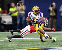 ATLANTA, GA - DECEMBER 7: Clyde Edwards-Helaire #22 of the LSU Tigers avoids a tackle by Tyrique McGhee #26 of the Georgia Bulldogs during a run during a game between Georgia Bulldogs and LSU Tigers at Mercedes Benz Stadium on December 7, 2019 in Atlanta, Georgia.