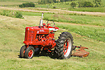 1953 Farmall Model M tractor with mower in a field in rural Iowa