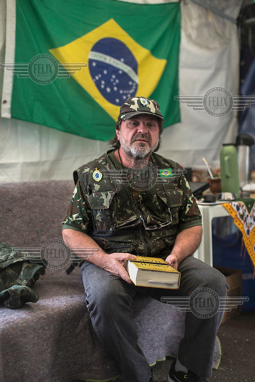 National Guards member Adans Ghizzi, of Campinas, holds a meeting with members of the Brazilian Interventionist Resistence Movement (MBRI) at their headquarters, called PR 1 -Sergeant Mario Kozel Filho Military Interventionist Camp, a radical group that wants military intervention in the government. <br /> <br /> Their headquarters is a makeshift tarpaulin camp situated on an island in the middle of Sergeant Mario Kozel Filho Avenue, between the State Legislative Assembly and the Ministry of the Military. <br /> <br /> Mr. Ghizzi holds a book, called Orvil (which is book spelled backwards in Portuguese ). After the end of the military dictatorship (1 April, 1964 to 15 March, 1985), a military commission produced a report on the events that occurred between 1964 and 1985 during the military's armed conflict with the left. It was developed in secrecy over three years and completed in 1988.