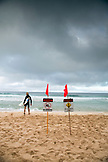 USA, Oahu, Hawaii, a surfer enters the water at Pipeline surf break on the North Shore of Oahu