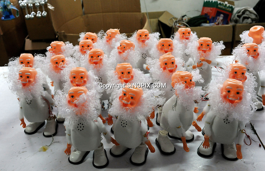 Dancing Santa's wait for their clothes to be put on at a medium sized factory in Yi Wu, China.  Yi Wu exports 40-50 % of the entire European Christmas decorations and 70 % of US and Mexico's Christmas gifts come from Yi Wu.