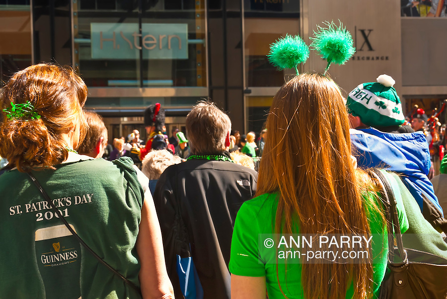 MARCH 17, 2011 - MANHATTAN; Seen from back, Crowd watching St. Patrick's Day Parade on 5th Avenuue and E 51 Street, with one girl wearing two fuzzy green balls on headband (deely boopers), and another girl wearing St. Patrick's Day 2001 Guinness shirt, and baby wearing Irish hat.