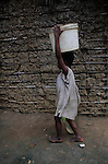A girl carries water over head in Masue Masue. In many developing countries children seen in the need to work to have access to the most basic things, help their families, go to school, food or water are just some of them.