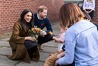 06/11/2019 - Meghan Markle Duchess of Sussex receiving a posy of flowers from Bonnie and Maggie Emanuel (mother and daughter) with Prince Harry Duke of Sussex, during a visit to Broom Farm Community Centre in Windsor. The Duke and Duchess of Sussex attended a coffee morning with families of deployed Army personnel at the Centre. Photo Credit: ALPR/AdMedia