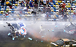 Spectators duck and shield themselves from debris from Kyle Larson's #32 Clorox Chevrolet as it  disintegrates from a wreck on the way to the finish line on the final lap of the NASCAR Nationwide Series DRIVE4COPD 300 auto race at Daytona International Speedway in Daytona Beach, Florida February 23, 2013. Twenty-nine spectators were injured in the stands.<br />