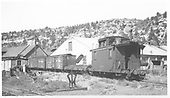 RGS Dolores yards with two box cars, a flat and a caboose.  Section car shed and feed elevator are in background.<br /> RGS  Dolores, CO  Taken by Richardson, Robert W. - 10/10/1945