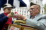 "Zev Mondry, 3, offers a cash donation while accepting a ""Buddy Poppy,"" small paper flowers made by disabled veterans, from Elmer Cox, 90, during the Dane County Farmers' Market around Capitol Square in downtown Madison, Wis, on May 17, 2003. Cox is a member of Wisconsin V.F.W. 1318 and a veteran of both World War II and the Korean War."