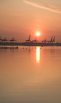 Sunrise over cranes of Port of Felixstowe, Suffolk, England viewed from Harwich,