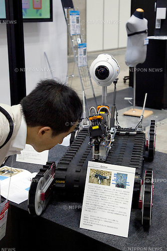 October 17, 2012, Tokyo, Japan - Visitor sees a prototype robot with camera at Japan Robot Week. The Japan Robot Week 2012 shows the New Energy and Industrial Robot Innovation Technology products in Japan, the exhibition opens from October 17 to 19 at Tokyo Big Sight. (Photo by Rodrigo Reyes Marin/AFLO)..