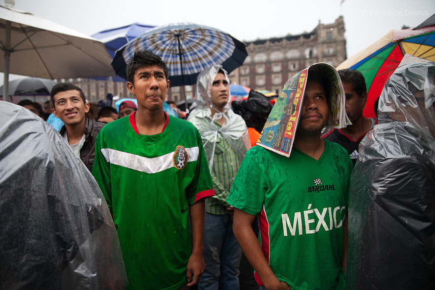 Thousands of fans gather under the rain to watch the transmission of the 2014 World Cup soccer match between Croatia and Mexico at the Zocalo main square in Mexico City on June 23, 2014. Mexico qualify from Group A with three late goals against Croatia. (Photo by Bénédicte Desrus)