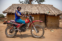 Healer Dominga Joao Antonio (35) astride a motorcycle outside her house.