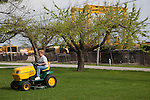 Diane Gifford shares yard mowing duties with her husband Bruce. The retirees have lived in their Decatur home for over 40 years, and raised three kids there. The house is across the street from Caterpillar and Keen Transport, shown in the background. Gifford says that because of the truck dust she has to clean her kitchen before making dinner, and she can't hang clothes to dry. Longtime industrial city Decatur, Ill., had the country's greatest unemployment rate reduction. But people leaving the workforce – moving away, retiring, no longer looking for jobs -- may be the cause, rather than economic expansion. <br /> CREDIT: Kristen Schmid for the Wall Street Journal<br /> RUSTBELT