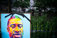 NEW YORK, NEW YORK - June 25: NYPD officers stand guard inside NYC City Hall as a picture of George Floyd holds on a fence while Demonstrators take part in a protest encampment near NYC City hall on June 25, 2020 in New York, NY. Demonstrators are calling for $1 billion in cuts of NYPD, as they protest encampment near City Hall and NYPD headquarters ahead of the city July 1 budget deadline.  (Photo by Eduardo MunozAlvarez/VIEWpress)