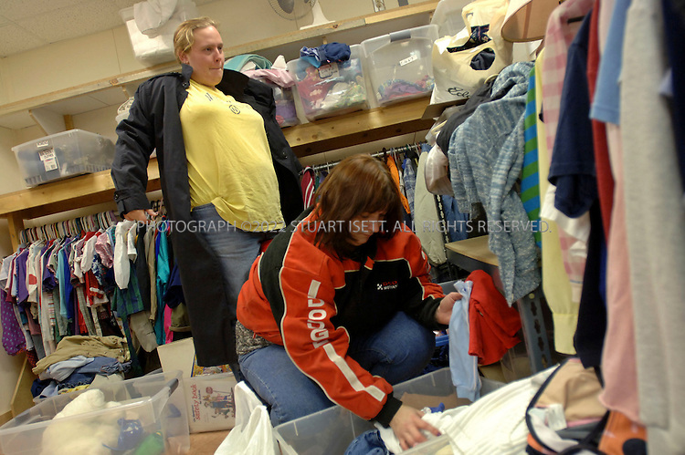 11/10/2006--Hamilton, WA, USA..Tracey Wyatt (front) and Jessica Fell (behind) search through donated clothes at an emergency center in Hamilton after the town was recently hit by a flood. With a population of about 330 people, Hamilton is a  flood-prone town on the Skagit River that some local residents want the town moved away from the river...Photograph By Stuart Isett.All photographs ©2006 Stuart Isett.All rights reserved.