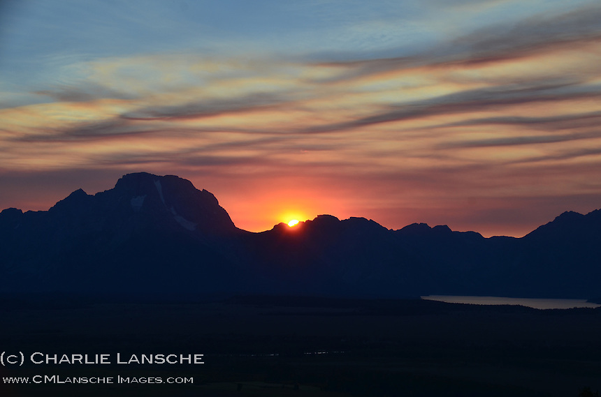 The summer sun slips over Mt. Moran and the Teton Range and Jackson Lake from my camp in Bridger National Forest, Wyoming.  July 2012.