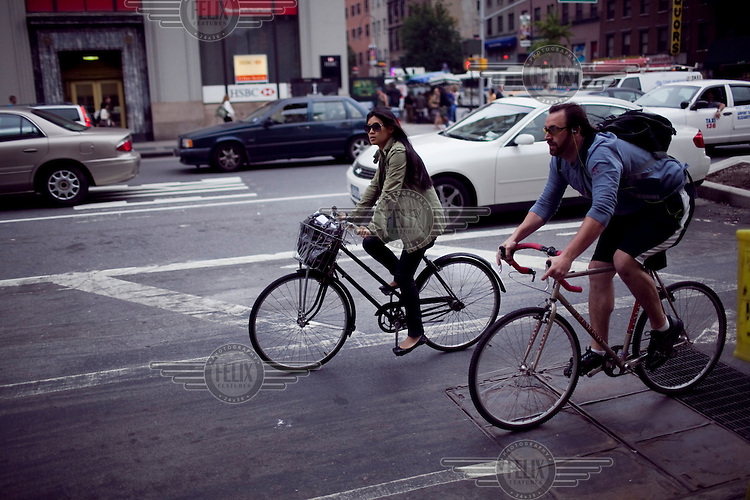 People ride bicycles on a busy street past an HSBC bank in Chelsea, New York.