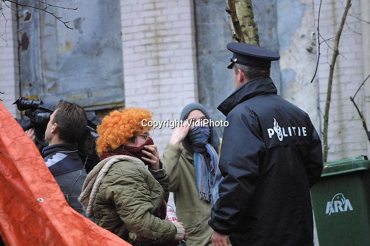 """Foto: VidiPhoto..ARNHEM - De politie heeft dinsdag het laatste krakersbolwerk van Arnhem en één van de oudste kraakpanden van Nederland ontruimd. Het """"Katshuis"""" is 21 jaar het onderkomen van de kraakbeweging geweest. Het kostte de politie de nodig moeite om de ongeveer tien krakers uit het pand te krijgen. Behalve dat ze de deuren gebarricadeerd hadden, zaten ze ook vastgeketend aan allerlei objecten in de woning. Het Katshuis is vorig jaar zomer omgekocht door de naastgelegen discotheek EntreNous. Foto: Twee kraaksters komen uit het pand."""