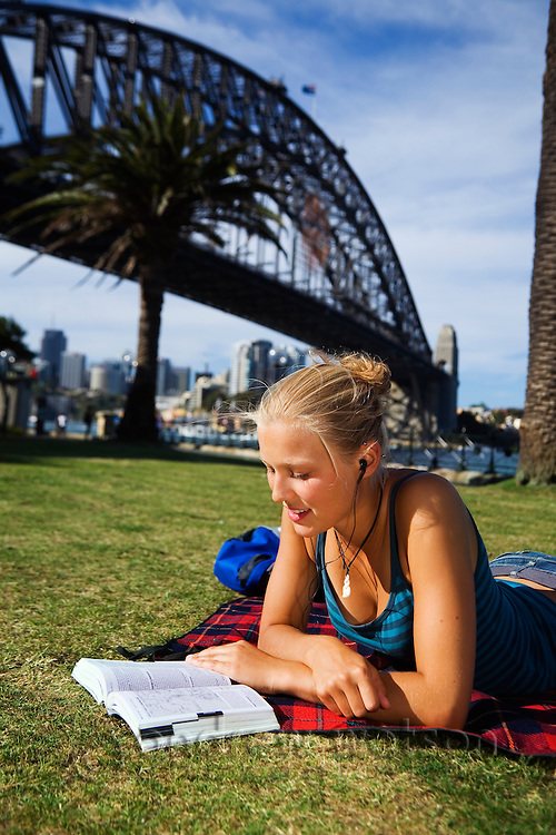 A young woman reads a book on the lawn at Dawes Point Reserve on Sydney harbour.  Sydney, New South Wales, AUSTRALIA